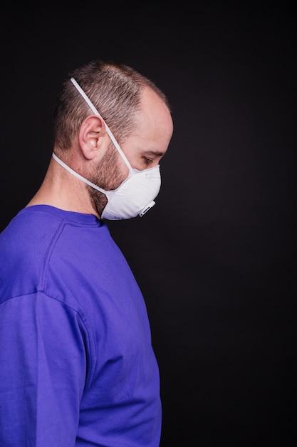 Immagine verticale di un uomo con una maschera su uno sfondo scuro - covid-19 Foto Gratuite