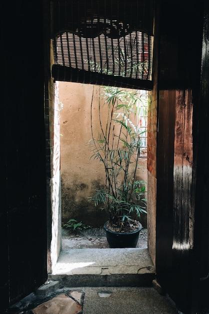 昼間の日光の下で古い建物のドアの垂直方向の写真 無料写真