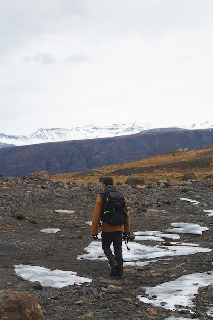Вертикальное изображение туриста с фотоаппаратом на холмах, покрытых снегом в исландии Бесплатные Фотографии