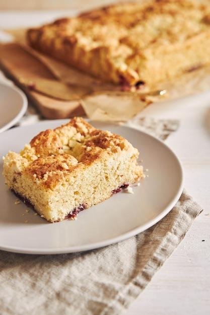 Вертикальное изображение куска восхитительного торта jerry crumble sheet на белом деревянном столе Бесплатные Фотографии