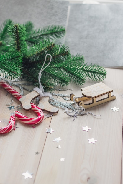 キャンディーとライトの下の木製のテーブルのクリスマスの装飾の垂直方向の画像 無料写真