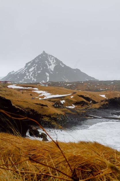 Immagine verticale di un fiume circondato da colline coperte di neve e vegetazione in islanda Foto Gratuite