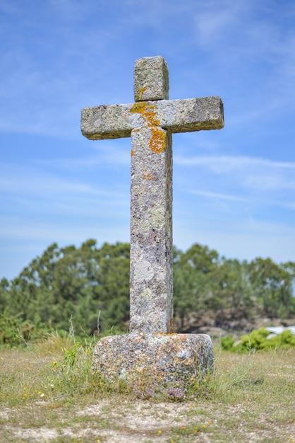 Immagine verticale di una croce di pietra ricoperta di muschi immersa nel verde sotto la luce del sole Foto Gratuite