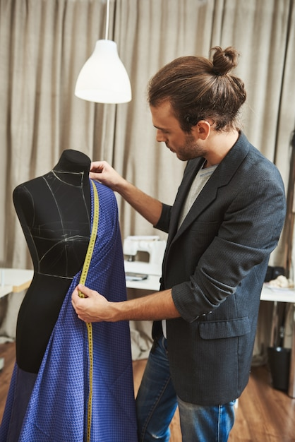 Vertical Portrait Of Adult Good Looking Caucasian Male Fashion Designer With Stylish Hairstyle In Fashionable Outfit In His Studio Working On New Dress For Winter Clothes Collection Free Photo
