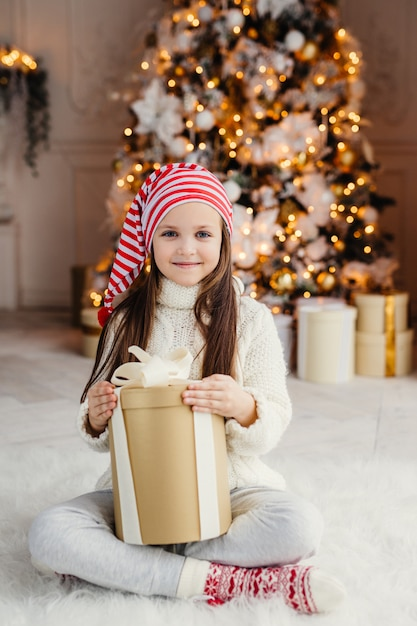 Vertical portrait of beautiful pleasant looking small child wears knitted sweater and socks, sits crossed legs with present, has desire to wrap it, being in living room near decorated new year tree Premium Photo