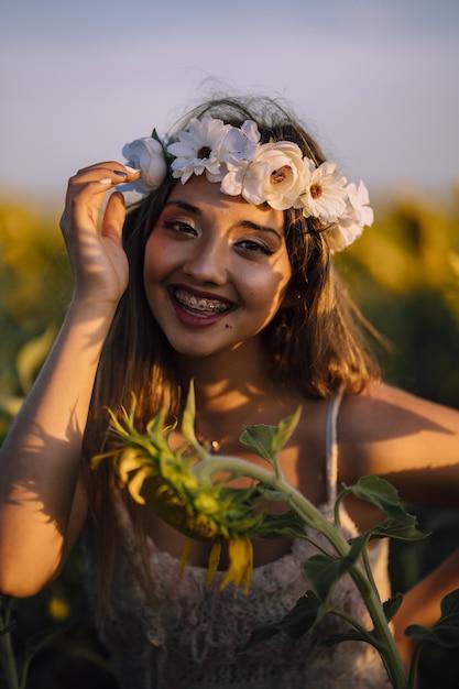 花のカラスの中かっこで縦向きの肖像画ブルネットの女性はひまわり畑で笑顔で前傾 無料写真