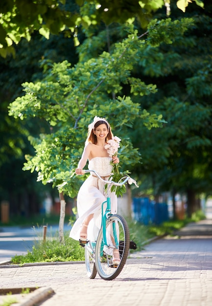 Вертикальный портрет женщины, весело улыбаясь, наслаждаясь на велосипеде в парке летом Premium Фотографии