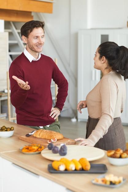 友人と屋内でディナーパーティー中にチャットする大人の男性と女性の縦の肖像画 Premium写真