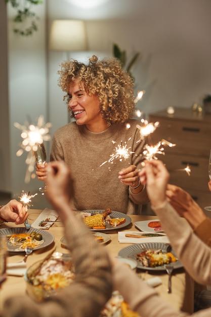 友人や家族とのディナーパーティーやお祝いを楽しみながら線香花火を保持しているのんきな混血の女性の縦の肖像画 Premium写真