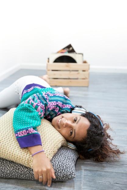 自宅で音楽を聴いているヒスパニック系女性の縦の肖像画。テキスト用のスペース。 Premium写真
