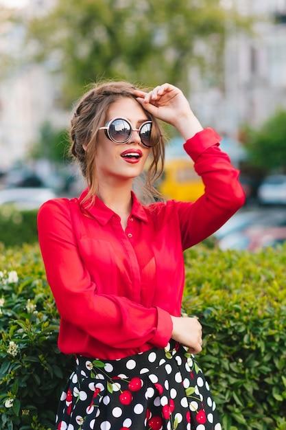 Вертикальный портрет красивой девушки в солнцезащитных очках, позирует перед камерой в парке. она носит красную блузку, черную юбку и красивую прическу. она смотрит далеко. Бесплатные Фотографии