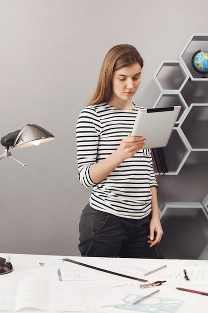 Вертикальный портрет молодой profeciaonnal красивой архитекторской девушки с каштановыми волосами в полосатой рубашке и черных джинсах, стоящих возле стола, смотрящих в цифровой стол, просматривающих клиента commisio Бесплатные Фотографии