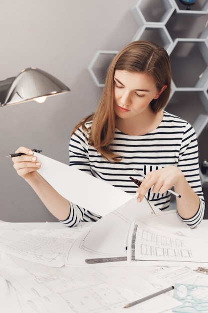 Download This Free Photo Vertical Portrait Of Young Good Looking Female Designer With Brown Hair In Striped Shirt Looking At Papers With Serious Expression Working On New Clothes Designs For Fashion Show
