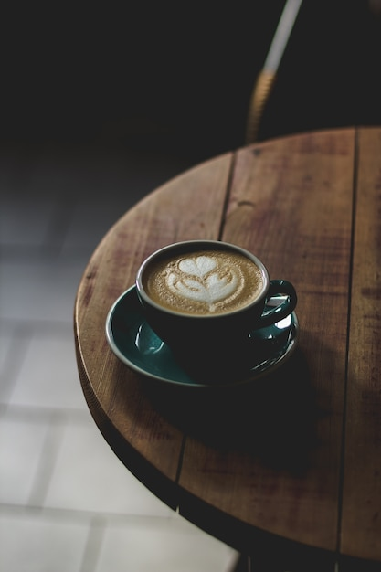 Vertical selective closeup shot of coffee with latte art in a blue ceramic cup on a wooden table Free Photo