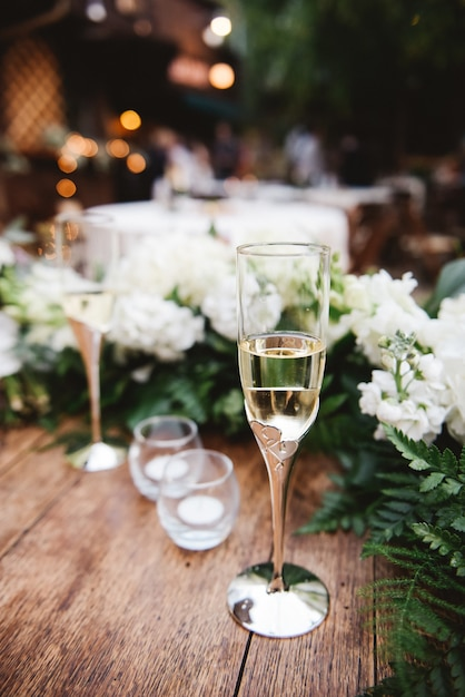Vertical selective focus shot of a glass of champagne on a wooden surface at a wedding Free Photo