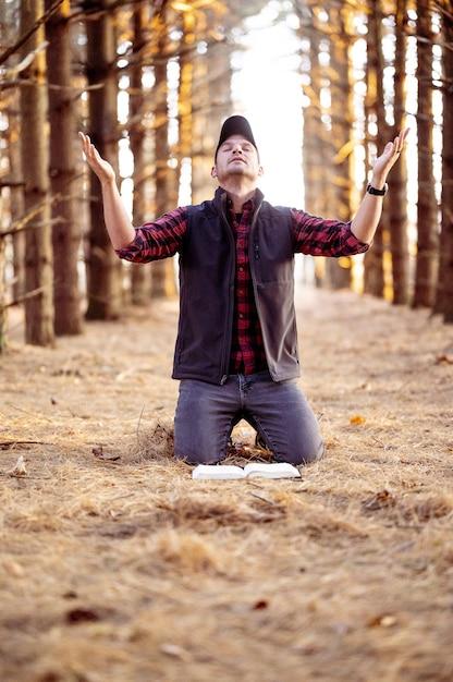 숲에서기도하는 남자의 수직 선택적 초점 샷 무료 사진