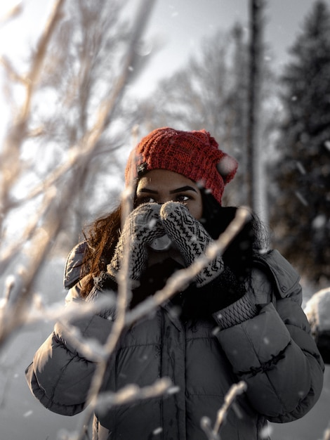 Vertical selective shot of a female wearing red hat, gloves and gray jacket during winter Free Photo