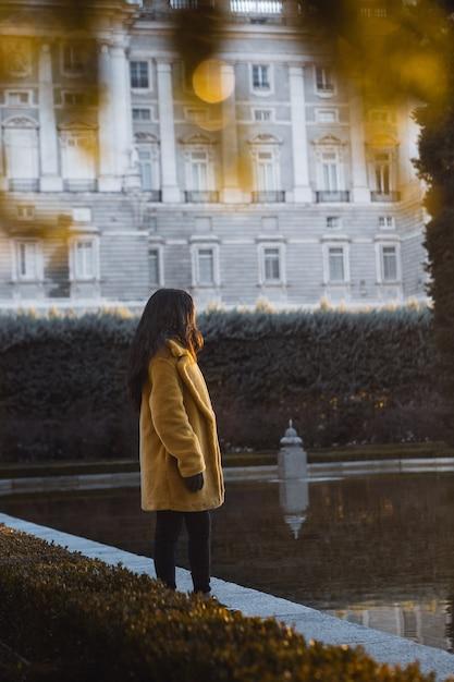 Colpo selettivo verticale di una femmina che porta cappotto giallo che fa una pausa l'acqua vicino ad una costruzione bianca Foto Gratuite
