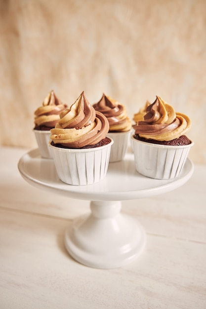 Vertical shallow focus closeup shot of delicious peanut butter cupcakes with creamy icing on a plate Free Photo