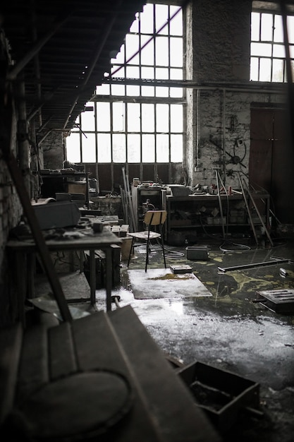 Vertical shot of an abandoned messy warehouse Free Photo