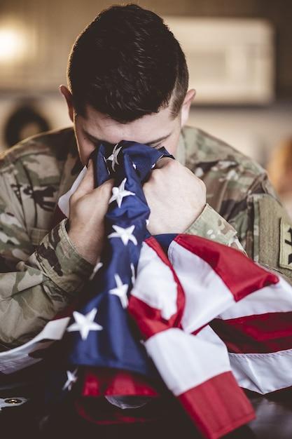 Colpo verticale di un soldato americano in lutto e in preghiera con la bandiera americana nelle sue mani Foto Gratuite