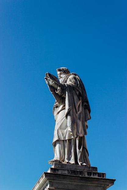 Colpo verticale di una statua storica antica che tocca il chiaro cielo blu Foto Gratuite