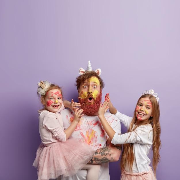 Colpo verticale di stupito uomo dai capelli rossi indossa corno di unicorno, gioca con due bambine, si diverte con i colori, dipinge volti e vestiti, è di buon umore, isolato su un muro viola. concetto di famiglia Foto Gratuite