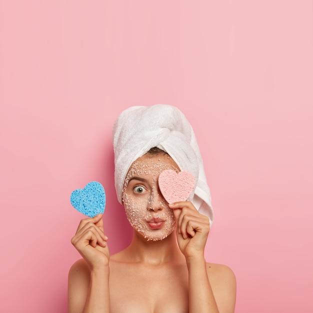 Colpo verticale di giovane donna stupita che copre un occhio con una spugna cosmetica, ha un trattamento viso mattutino, applica una maschera al sale marino bianco per una pelle impeccabile, assorbe i nutrienti Foto Gratuite