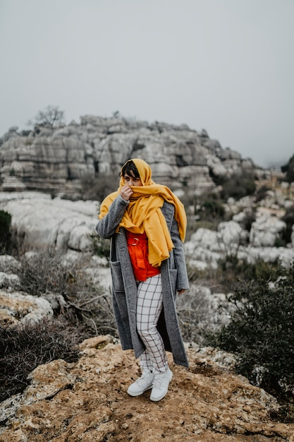 Vertical shot of an attractive young female with a coat and a red scarf posing on top of a cliff Free Photo