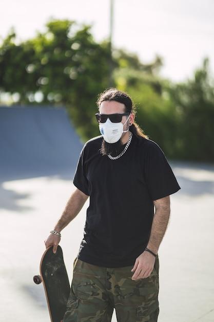 Colpo verticale di un maschio barbuto che indossa la maschera per il viso a piedi al parco mentre si tiene il suo skateboard Foto Gratuite