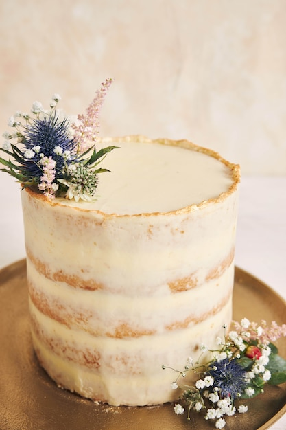 Colpo verticale di una bella e deliziosa torta con fiori e bordi dorati su sfondo bianco Foto Gratuite
