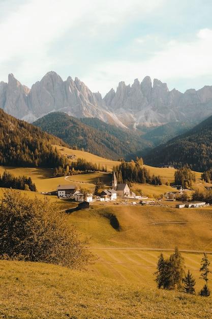 Scatto verticale di un bellissimo villaggio su una collina circondata dalle montagne Foto Gratuite