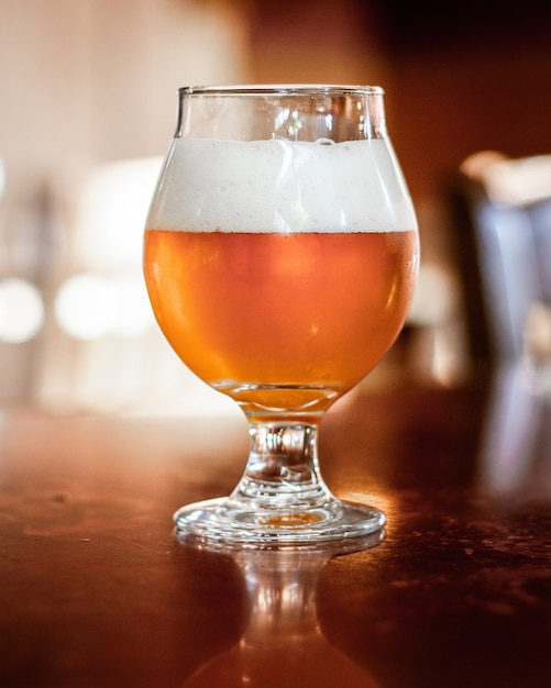 Vertical shot of beer in a glass cup with a blurred background Free Photo