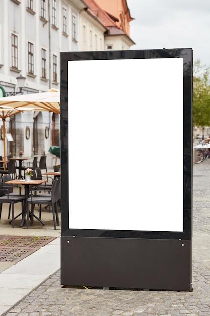 Il colpo verticale del tabellone per le affissioni in bianco sta sul pavemenet contro il fondo della città vicino alla caffetteria all'aperto Foto Gratuite