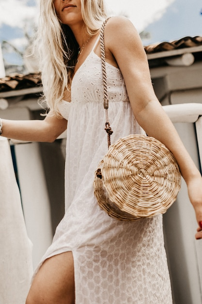 Vertical shot of a blonde woman in a white dress with a straw bag on her shoulder Free Photo