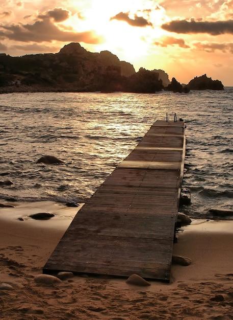 Colpo verticale di una passerella sulla spiaggia con uno splendido tramonto Foto Gratuite