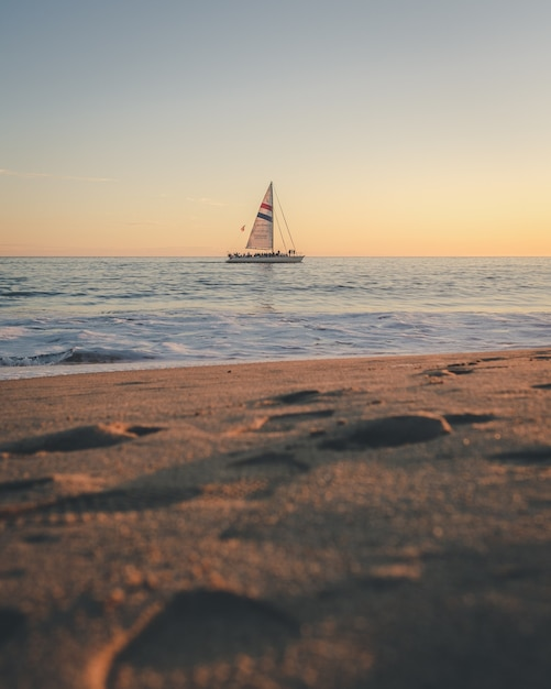 Vertical shot of a boat on the sea in the distance Free Photo