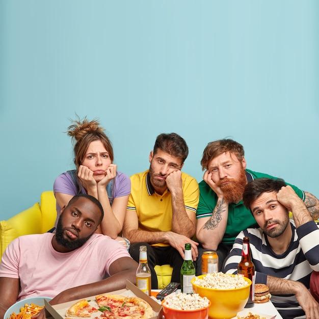 Colpo verticale di ragazzi annoiati che guardano programmi noiosi in televisione, trascorrono il tempo libero a casa, aspettano film interessanti, si divertono a bere birra e mangiare fast food. concetto di cinema domestico Foto Gratuite