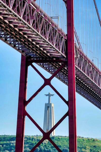 Colpo verticale di un ponte con la statua di cristo a lisbona, portogallo Foto Gratuite