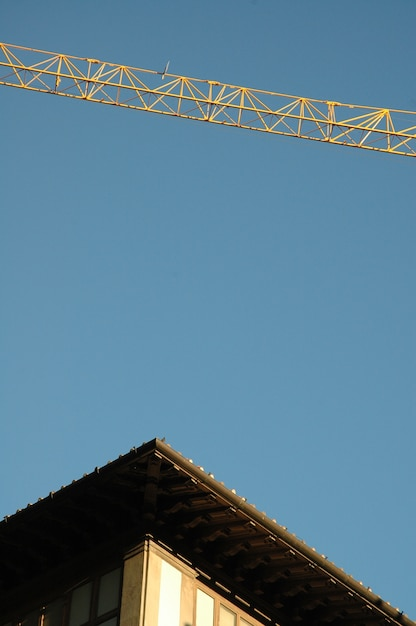 Vertical shot of a building's roof and a crane with a clear sky Free Photo