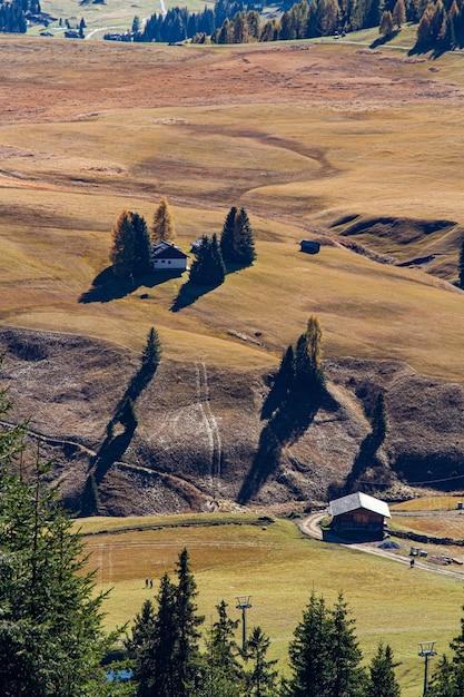 Colpo verticale di edifici su una collina erbosa in dolomia italia Foto Gratuite