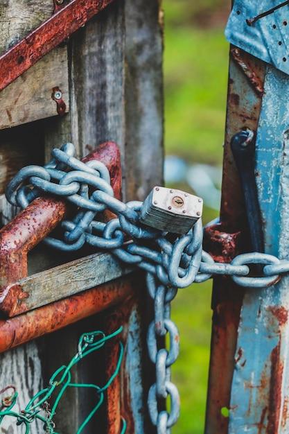 Colpo verticale di un lucchetto a catena del cancello Foto Gratuite