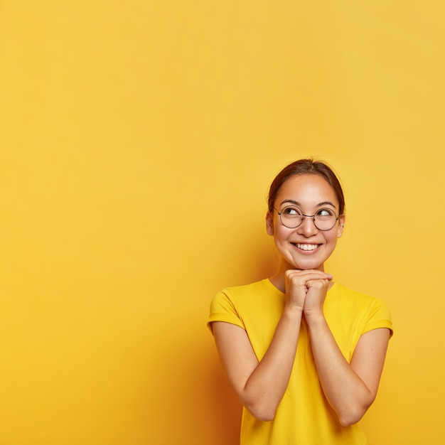 Vertical shot of cheerful thoughtful asian female keeps hands pressed together under chin, hopes for something awesome, wears spectacles and t shirt, has natural beauty, isolated on yellow  wall Free Photo