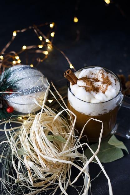 Colpo verticale di un caffè di natale con cannella e schiuma, accanto a ornamenti natalizi Foto Gratuite