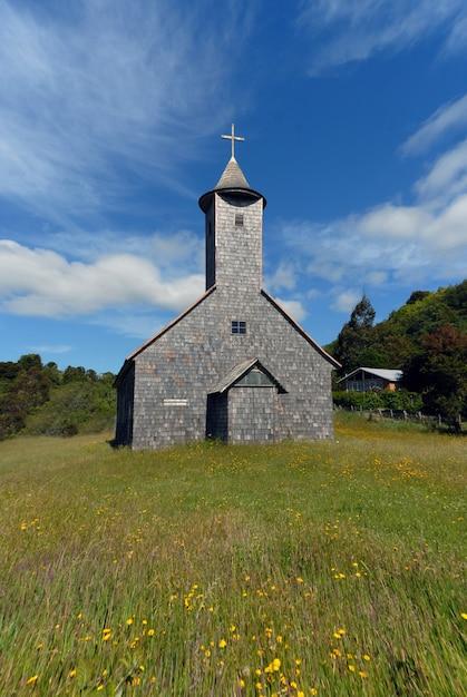 Colpo verticale di una chiesa in un campo erboso sotto un cielo blu Foto Gratuite