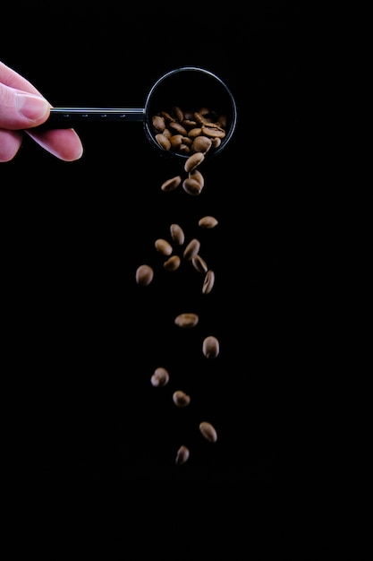 Vertical shot of coffee beans dropping from a coffee scoop isolated on black Free Photo