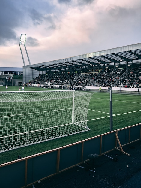 Vertical shot of crowded soccer stadium under cloudy sky Free Photo