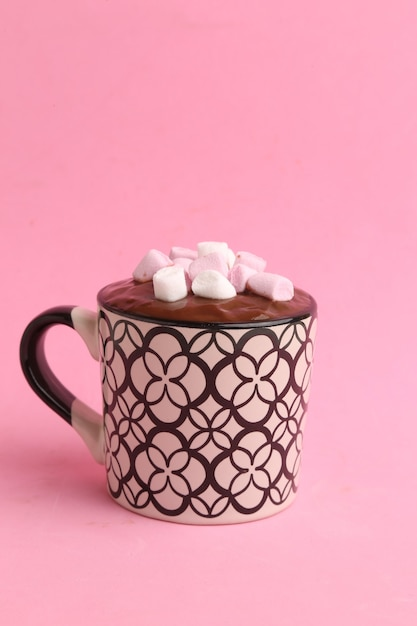 Vertical shot of a cup of hot chocolate with marshmallows isolated on a pink background Free Photo