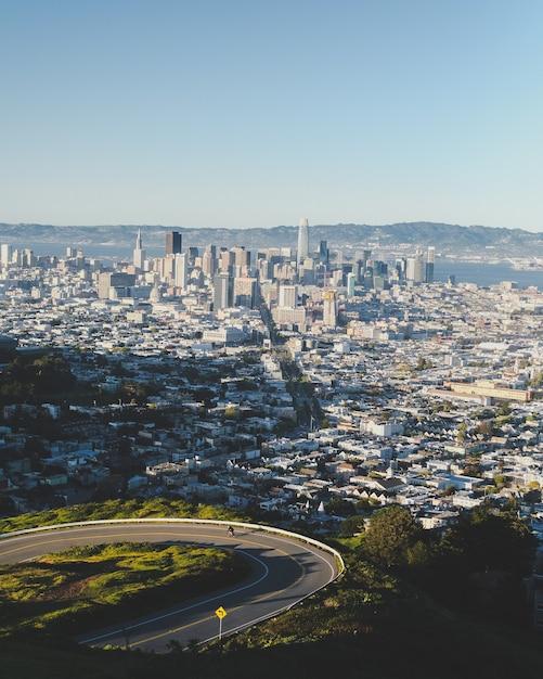 Colpo verticale di una strada sinuosa giù per la collina con edifici della città in lontananza sotto un cielo blu Foto Gratuite