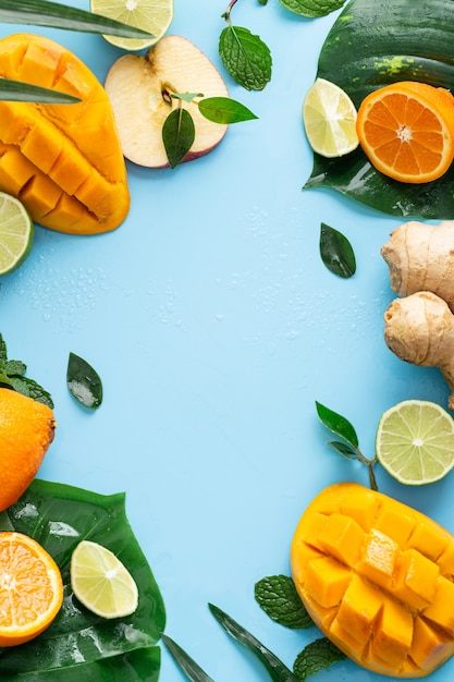 Vertical shot of cut fruits on a light blue background Free Photo